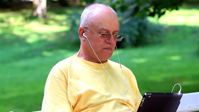 Senior man enjoying music on his digital tablet pc video