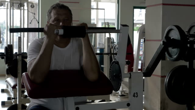Senior man exercising on bicep training machine video