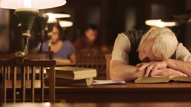 DS Senior man falling asleep on the book in library video
