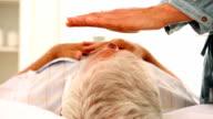 Senior man getting reiki therapy video