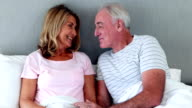 Senior man giving gift to woman in bedroom video