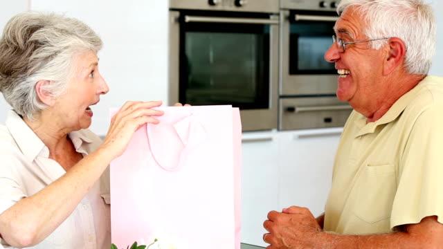 Senior man giving partner a present in pink bag video