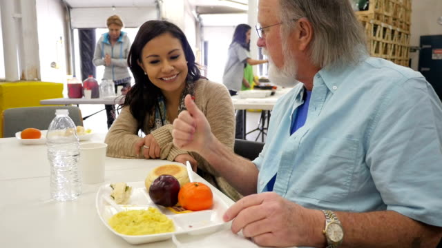 Senior man having meal in soup kitchen with young volunteer video