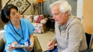 Senior man in assisted living facility meeting with staff nurse to discuss injury and healthcare video