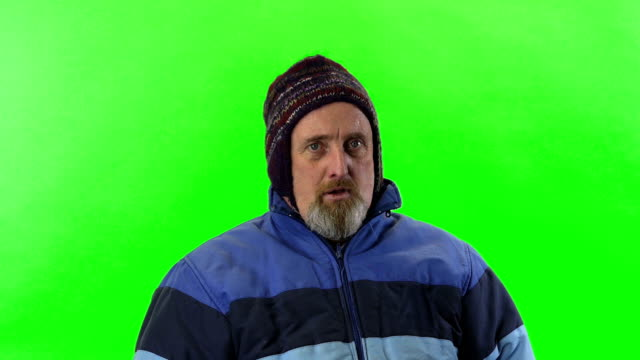 senior man in hat and coat on chroma screen video