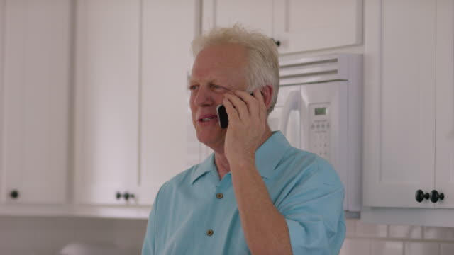 Senior man in kitchen on cell phone video