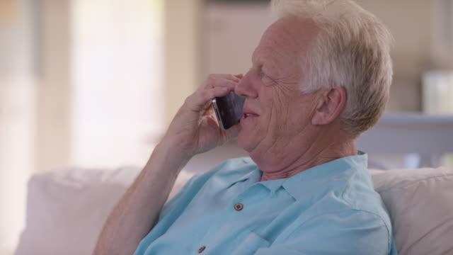 Senior man in living room talking on cell phone video
