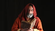 Senior Man In Medieval Priest Costume Reading Bible video