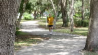 Senior man jogging in park and gesturing towards to camera video