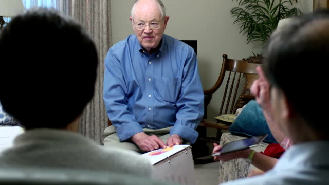 Senior Man Leads a Group Financial Discussion video