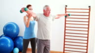 Senior man lifting hand weights with help of trainer video