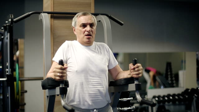 Senior man lifting weights of his body in the gym video