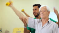 Senior man lifts up the dumbbell at the hospital video