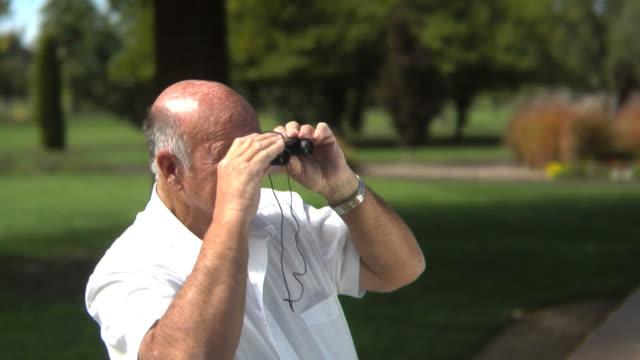 Senior man looking through binoculars video