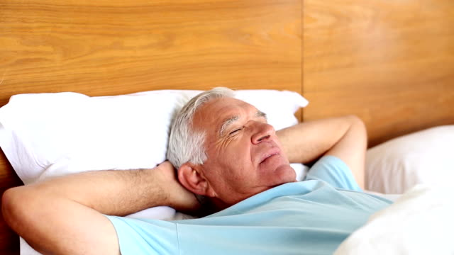 Senior man lying in bed sleeping video