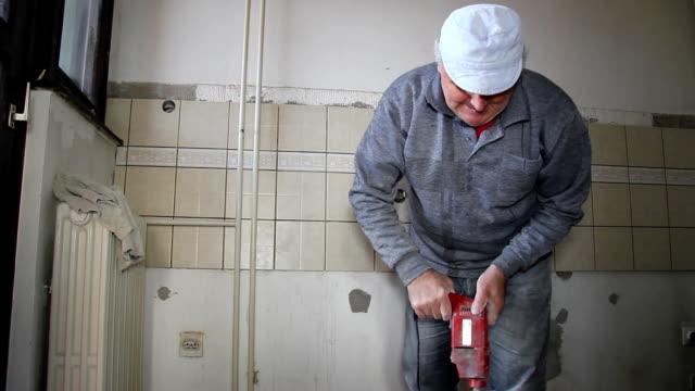 Senior man mixing adhesive for ceramic tiles video