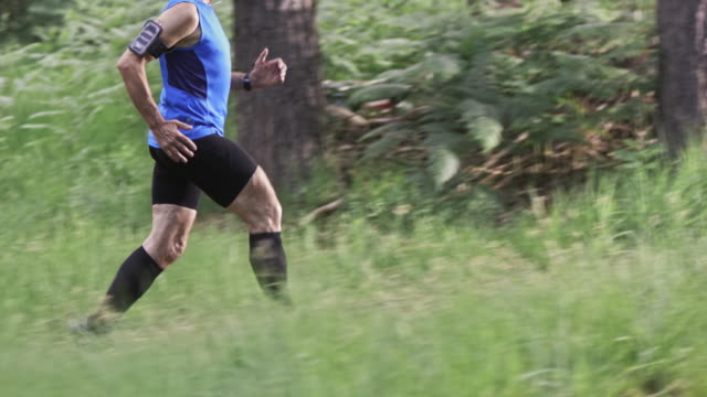 SLO MO DS Senior man on his run through forest video
