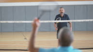 Senior man playing indoor badminton with male friend video