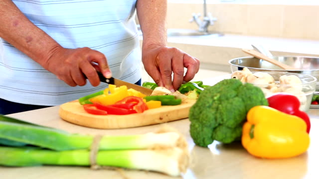 Senior man preparing vegetables for dinner video