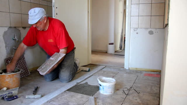Senior man putting tiles on the floor video
