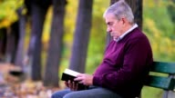 Senior man reading a book in the park video