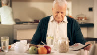 Senior man reading newspaper at the table for breakfast video