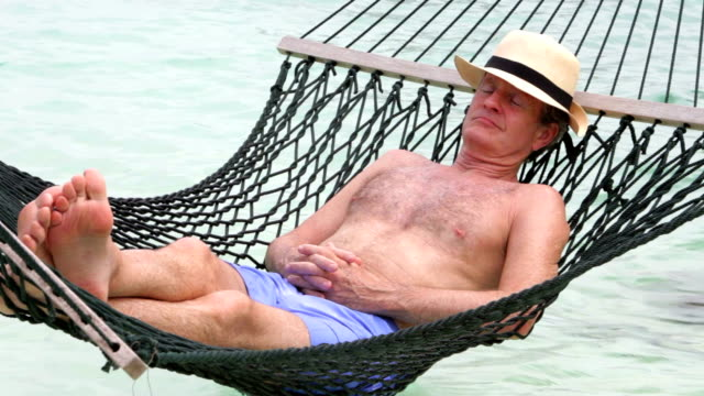 Senior Man Relaxing In Beach Hammock video