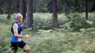 SLO MO DS Senior man running a marathon through the forest video