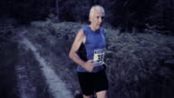 SLO MO DS Senior man running in marathon at sunset video