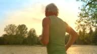 SLO MO TS Senior man running along lake at sunset video