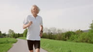 SLO MO TS Senior man running happily through countryside video