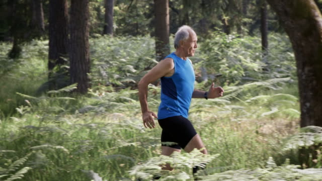SLO MO DS Senior man running in the forest video