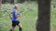 SLO MO DS Senior man running on forest trail video