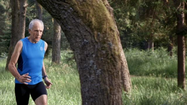 SLO MO DS Senior man running through forest in sunshine video