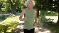 SLO MO TS Senior man running through park in sunshine video