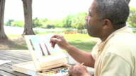 Senior Man Sitting At Outdoor Table Painting Landscape video