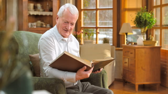 Senior man sitting in chair and looking at photo album video