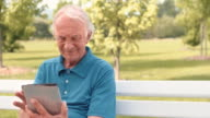 Senior man sitting on bench reading newspaper on a tablet video