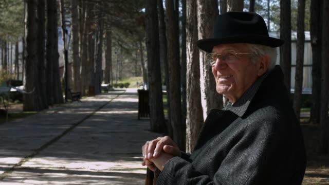 senior man sitting on park bench video