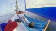 Senior man sleeping in hammock on sailing yacht, vacation, rest video