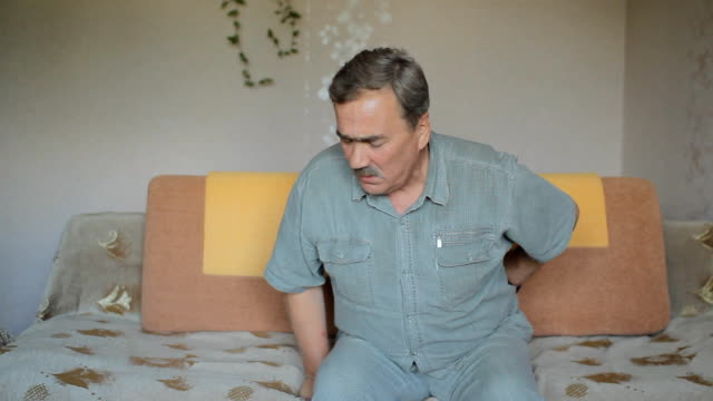 Senior man suffering from back pain at home video
