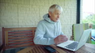 Senior man surfing on internet outside the house sitting on the porch video