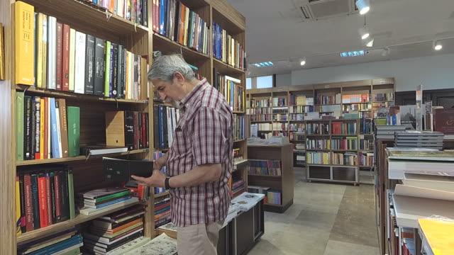 Senior man taking a book off a library shelf video