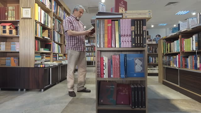 Senior man taking a book off a library shelf video