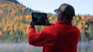 Senior Man Taking Picture of Lake Nature with Digital Tablet video