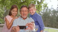 SLO MO Senior man taking selfies with his two grandkids video