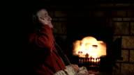 Senior man talking on mobile phone near fireplace video