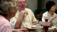 Senior Man Talks while Dining with Friends video