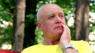 Senior man thinking about something outdoors video