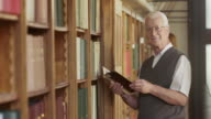 TU Senior man thumbing through a book in library video